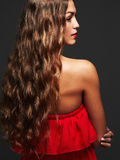 Beautiful girl with make-up.elegant lady in red dress. Back view of brunette woman with long curly hair posing at studio.Beautiful girl with make-up.elegant lady Royalty Free Stock Photos
