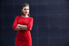 Beautiful girl with make-up in a red dress in a modern city Stock Image