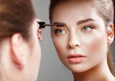 Beautiful girl makes herself a make-up in the mirror. Beauty face. Photo taken in studio Stock Photography
