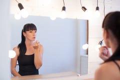 Beautiful girl makes herself the makeup Stock Image