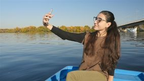 Beautiful girl makes selfie in the boat. Model appearance. Pretty smile. Scenic landscape. HD stock footage