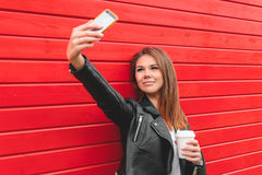 Beautiful girl makes selfie. Beautiful young woman in a black leather jacket makes selfie on a red wooden wall Royalty Free Stock Photos