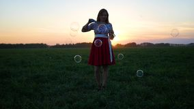 Beautiful girl makes soap bubbles at sunset stock video