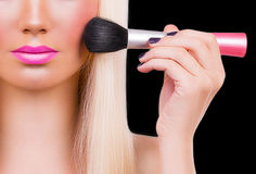 Beautiful girl with makeup brush Royalty Free Stock Images