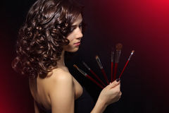 Beautiful girl with makeup brushes Stock Photography