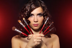 Beautiful girl with makeup brushes Stock Image