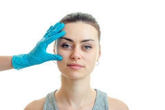 Beautiful girl without makeup came to the beautician who checks her face in blue gloves. On a white background Royalty Free Stock Image