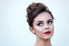 Beautiful girl with makeup and coiffure isolated on a light back Royalty Free Stock Photos