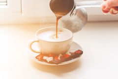 Woman`s hand pours fragrant coffee into a cup stock photo