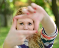 Beautiful girl making frame with hands while outdoors Stock Photo