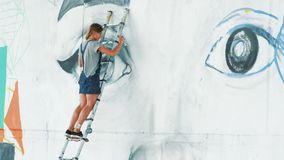 Beautiful girl making graffiti of big female face with aerosol spray on urban street wall. She standing on ladder