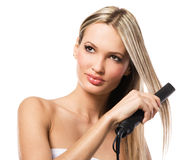 Beautiful girl making hairstyle with hair iron. Portrait of young beautiful girl making hairstyle with hair iron Stock Photo