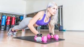 Beautiful girl making push ups on dumbbells Royalty Free Stock Image
