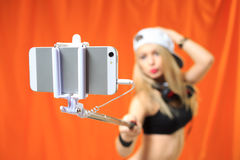 Beautiful girl making selfe photo on the phone with stick Royalty Free Stock Images