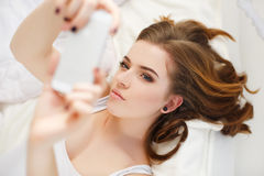 Beautiful girl making selfie in the bed. Stock Image