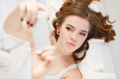 Beautiful girl making selfie in the bed. Royalty Free Stock Image