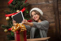 Beautiful girl making selfies on tablet PC near New Year tree Royalty Free Stock Photos