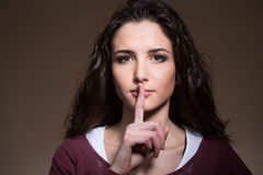 Beautiful girl making silence gesture Stock Photo
