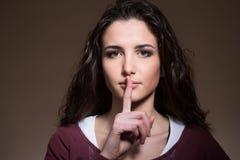 Beautiful girl making silence gesture Stock Photo