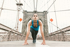 Beautiful girl making stretching at early morning before running. brooklyn bridge and new york skyline in the background. Beautiful girl making stretching at stock images