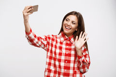 Beautiful girl making video calls with friends, waving left hand royalty free stock photo