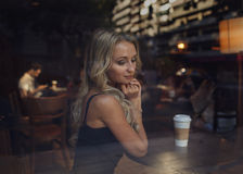 Beautiful girl and man in the cafe. Blind date. Beautiful blonde girl sitting at the cafe with a cup of coffee and a figure of man behind her on the background stock photos