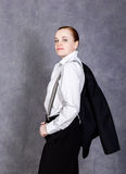 Beautiful girl in man`s suit, white shirt and suspenders poses on a gray background stock images