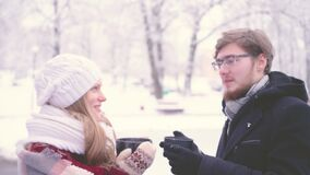 Beautiful girl and man talking and smiling while standing with cups of hot cocoa in their hands in the winter park. 4K stock video