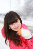 Beautiful girl with mandarin in hand. Beautiful girl mandarin in hand in the winter woods Royalty Free Stock Image