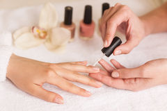 Beautiful girl manicurist doing manicure for woman in beauty salon. Stock Image
