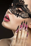 Beautiful girl in a mask with long fingernails. Royalty Free Stock Photography