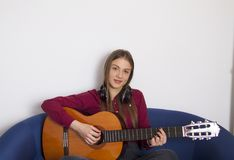 A beautiful young girl in a red shirt plays on an acoustic guitar. A beautiful girl may learn to play or know how to play perfectly.But she is a great fan of stock photos