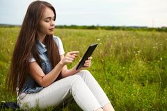 Beautiful girl in a meadow in the morning. The girl in the sunny morning in a meadow. Tablet Stock Photos