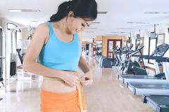 Beautiful girl measuring her waist in gym center. Beautiful girl measuring her waist by using a measure tape while standing in the gym center Royalty Free Stock Image