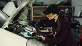 Beautiful girl mechanic, brunette, in a plaid shirt and cap, in protective glasses repairing a car engine. The concept stock video footage