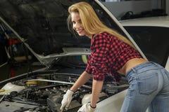 Beautiful girl mechanic. Repairing a car Royalty Free Stock Photos