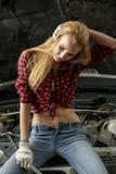 Beautiful girl mechanic. Repairing a car Royalty Free Stock Image