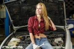 Beautiful girl mechanic. Repairing a car Royalty Free Stock Photography