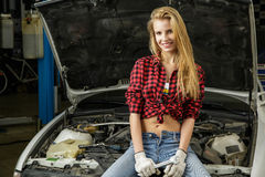 Beautiful girl mechanic repairing a car Stock Images