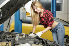 Beautiful girl mechanic repairing a car Stock Image