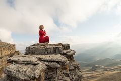 A beautiful girl meditates in a lotus pose sitting on a rock above the clouds against the backdrop of the sunset Stock Photo
