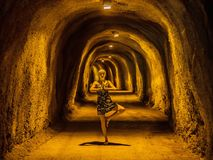 A beautiful girl meditates in a tunnel through the mountains.