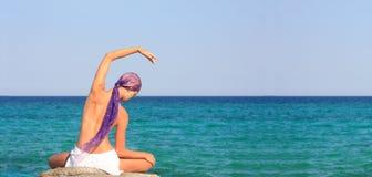 Beautiful girl meditating on the beach Stock Photo