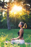 Beautiful girl meditating in forest on sunny summer day Stock Image