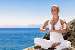 Beautiful girl meditating in yoga pose. Beautiful positive girl clothing in white sit at the seaside on the rock and meditating in yoga pose Stock Photo