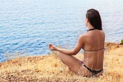 Beautiful girl in a meditation on the beach Royalty Free Stock Images