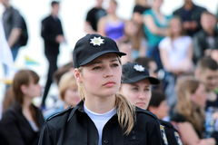 Beautiful girl, a member of the patrol police, on the city street. Royalty Free Stock Photography