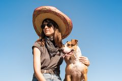 Beautiful girl in mexican hat dressed up as bandit of gangster w. Ith dog in cool sunglasses. Female person in sombrero hat and bandana posing with puppy as stock images