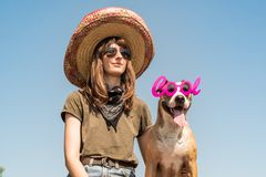 Beautiful girl in mexican hat dressed up as bandit of gangster w. Ith dog in cool sunglasses. Female person in sombrero hat and bandana posing with puppy as stock image