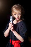 Beautiful girl with a microphone on stage Stock Images